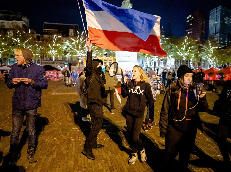 Demonstratie tegen de nieuwe coronamaatregelen, met een omgekeerde Nederlandse vlag, dinsdag op het Plein in Den Haag.  Beeld ANP