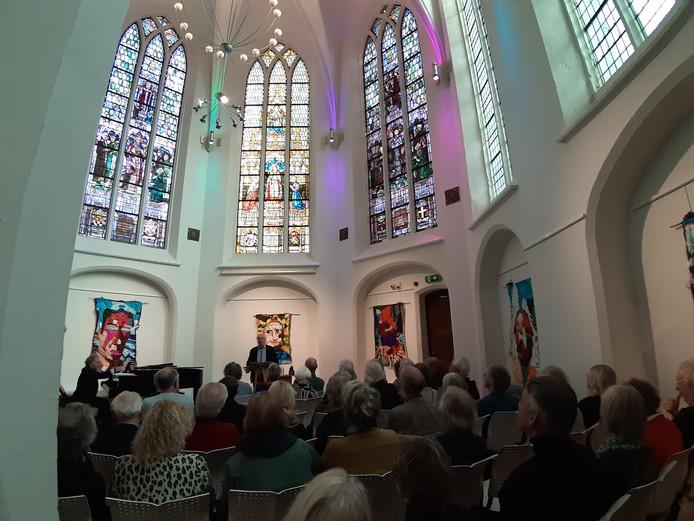 Jan Brokken vertelt in de Catharinakapel in Harderwijk over muziek en reizen, pianist Marcel Worms (l) speelde op de vleugel.