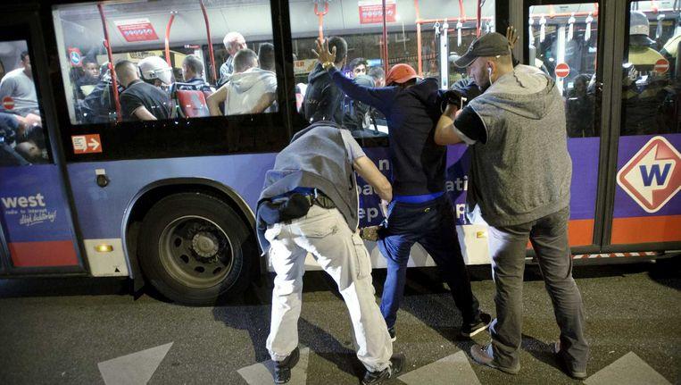 In totaal ongeveer honderd mensen worden gearresteerd, gefouilleerd en in arrestantenbussen afgevoerd op het Hobbemaplein in de Haagse Schilderswijk. Beeld anp
