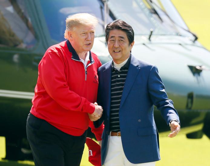 De Amerikaanse president Donald Trump (links) wordt verwelkomd door de Japanse premier Shinzo Abe, voordat de twee een rondje golf zullen spelen. Trump verblijft sinds zaterdag voor een vierdaags bezoek in Japan.