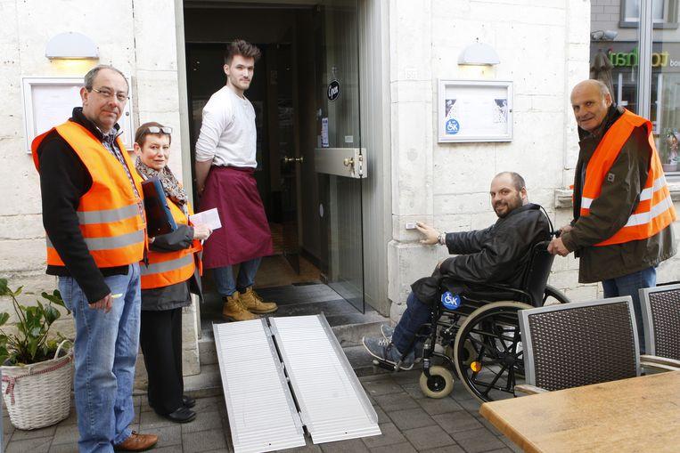 Leden van Toegankelijk Tienen testen hoe toegankelijk de zaak is voor rolstoelgebruikers.