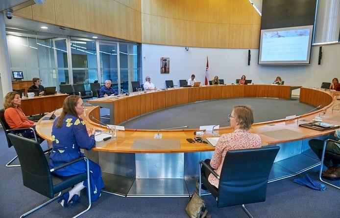 Onderzoekster Lauryan Bakker (tweede van links) van bureau Necker van Naem geeft in de raadszaal van Bernheze uitleg over het rapport over de zoektocht naar een passend huis voor Abdallah A..