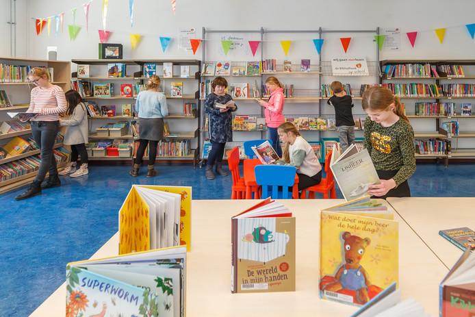 Leerlingen bekijken het boekenaanbod in de nieuwe schoolbibliotheek