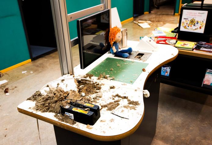 Verkruimelde stukken hardboard van plafondplaten liggen her en der in de jeugdafdeling van de Centrale Bibliotheek.