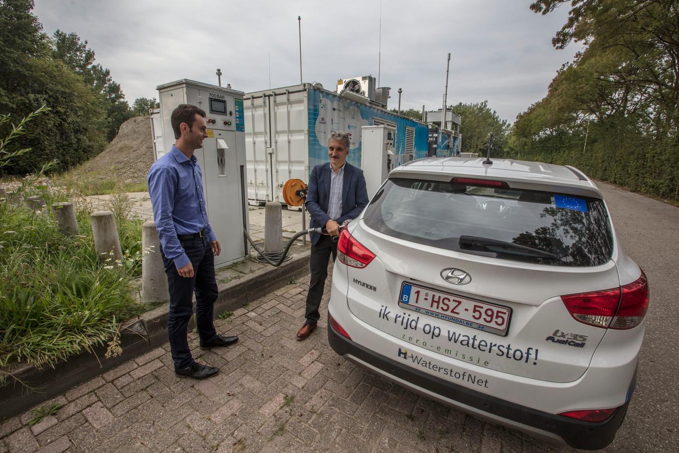 Adwin Martens tankt zijn auto vol met waterstof. Stefan Neis kijkt toe.