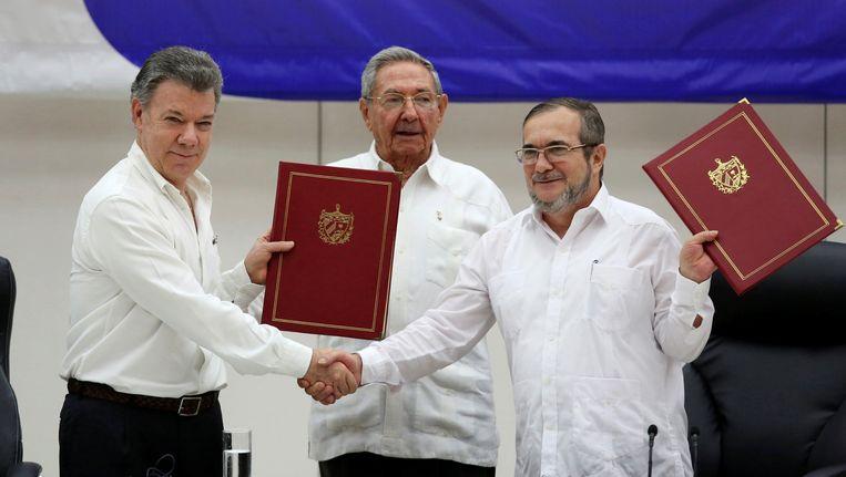 De Colombiaanse president Juan Manuel Santos schudt de hand van de FARC-leider Rodrigo Londono. Achter het duo staat de Cubaanse president Raul Castro. Beeld reuters