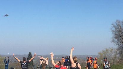 Wandelaars en fietsers zwaaien van boven op de Muur naar 'Ronde tegen Corona'-heli
