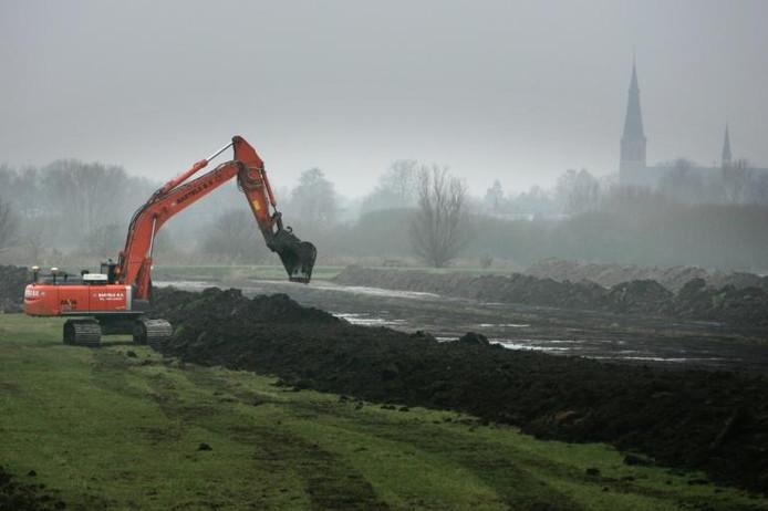 Afgraven van de bovenlaag voor nieuwe natuur in de Beemdenpolder. Op de achtergrond de kerk van Terheijden. foto's Ramon Mangold/het fotoburo
