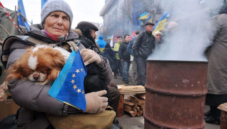 Een vrouw in Kiev met vlaggetjes van Oekraïne en de EU. Beeld AFP