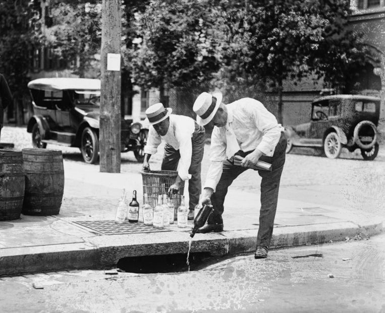 Agenten gooien drank de afvoer in, VS, ca. 1921. Beeld Getty