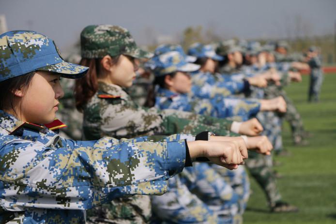 Chinese studenten van de Gongshang-universiteit leren tijdens een militaire training vuisttechnieken om zichzelf te kunnen verdedigen. Meer dan 1.700 studenten volgden afgelopen weekeinde een gevechtstraining. Foto VCG