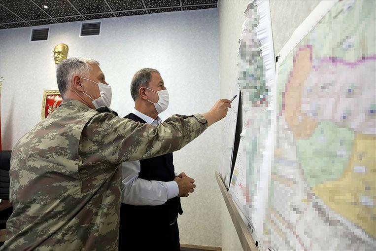 De Turkse minister van Defensie Hulusi Akar (rechts) bekijkt ontwikkelingen in de operatie Tijgerklauw.  Beeld AFP