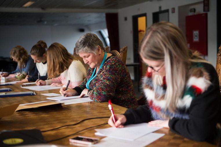 Deelnemers aan de actie 'Schrijf ze vrij' buigen zich geconcentreerd over hun handgeschreven brief.