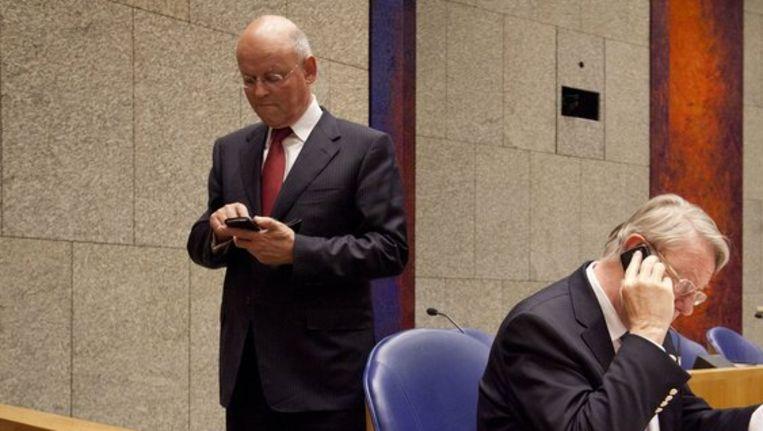 Ministers Hans Hillen en Uri Rosenthal telefoneren tijdens een korte pauze in de Tweede Kamer tijdens het debat over de Nederlandse bijdrage aan de missie in Libië. Beeld anp