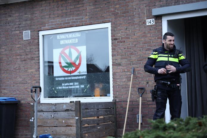 Een poster op het raam maakt duidelijk dat de hennepkwekerij in Arnhem is ontruimd en vernietigd.