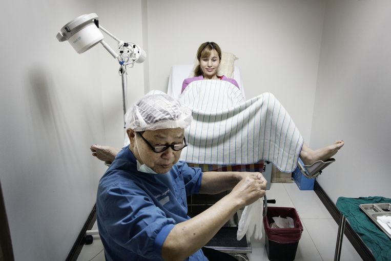 Dr. Preecha Tiewtranon maakt zich op voor een laatste controle van een recent door hem geopereerde vrouw. Beeld Daniel Rosenthal