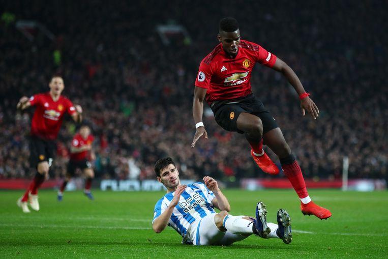 Paul Pogba springt over Christopher Schindler van Huddersfield Town en kan zijn tweede doelpunt van de middag bijschrijven. Beeld Getty