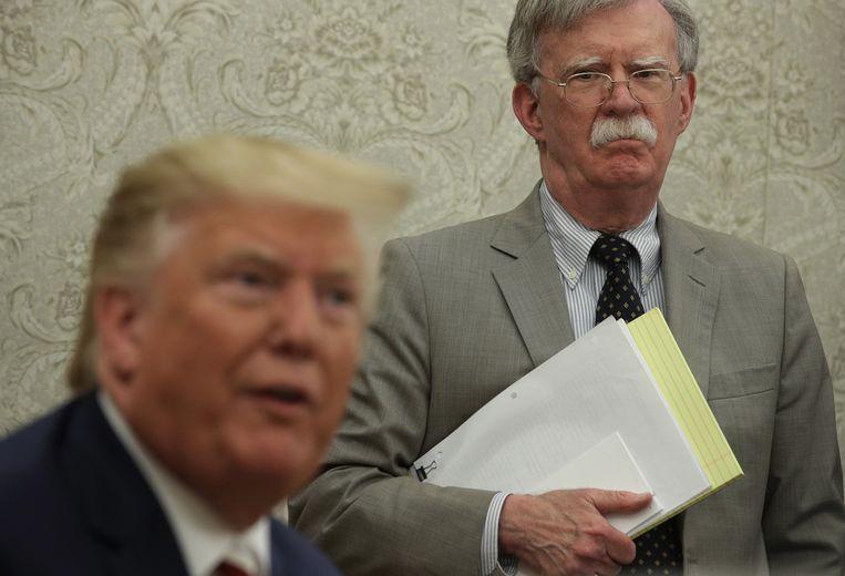 President Trump en op de achtergrond – toen nog – nationale veiligheidsadviseur John Bolton, op 20 augustus van dit jaar. Beeld Getty Images