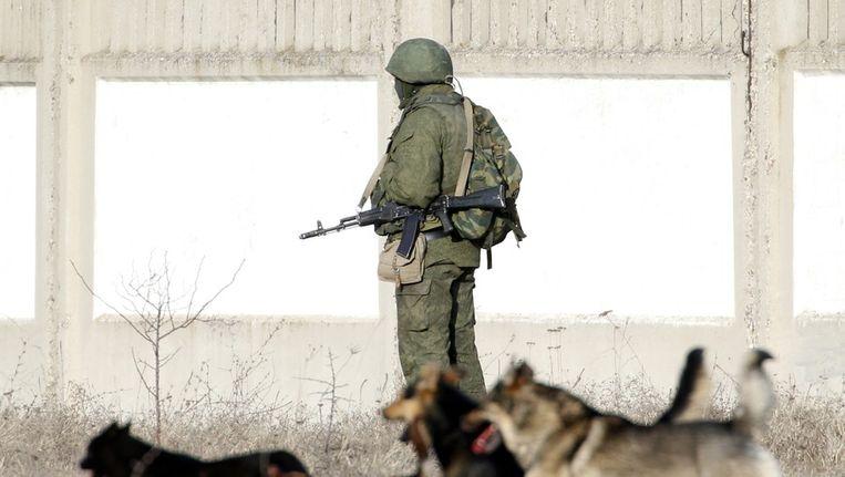Een gewapende man voor een militaire basis in het dorp Perevalnoye, buiten Simferopol. Beeld reuters