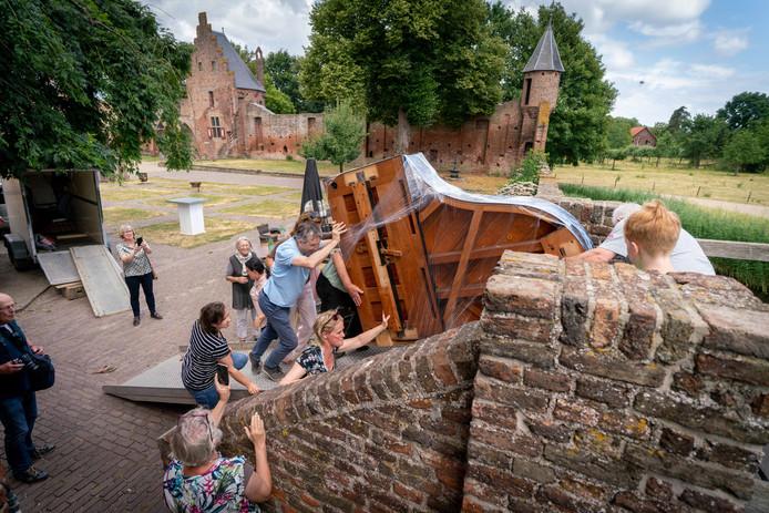 De antieke vleugel wordt op z'n kant de trap van kasteel Doornenburg opgeduwd.