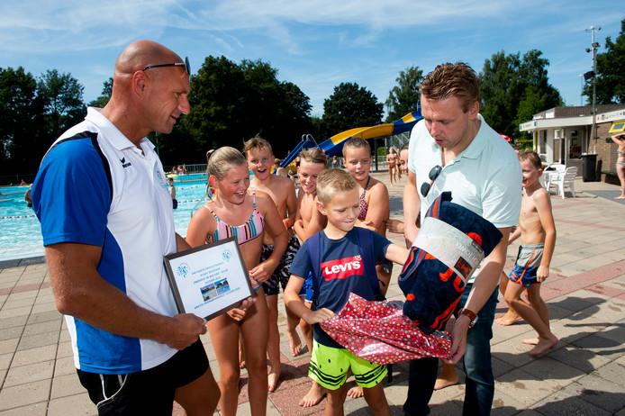 Bram de Vos is de 40.000e bezoeker van zwembad de Welters dit seizoen. Links Paul Balstra en rechts Wilco Roetert Steenbruggen.