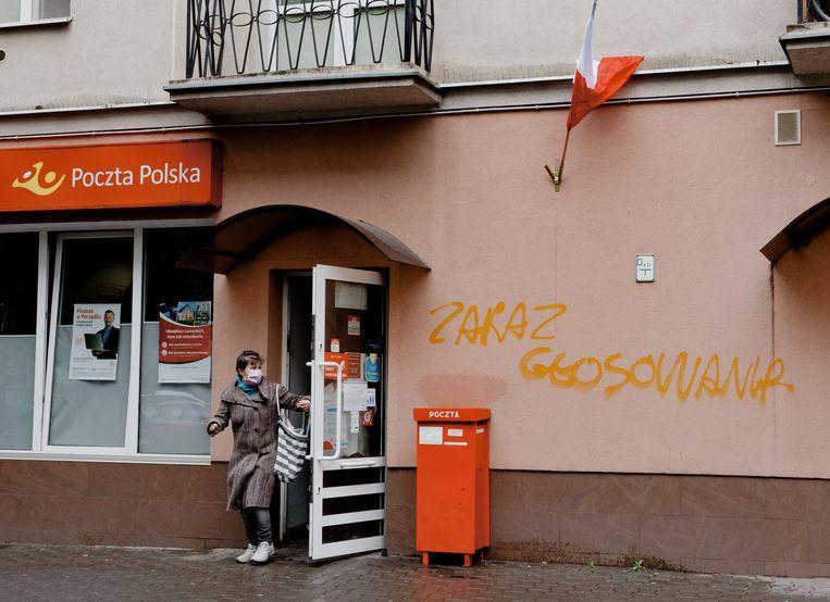 Een vrouw met een mondkapje loopt een postkantoor uit in de wijk Praga in Waschau, waar op de muur de leus 'Stemmen verboden' is gekalkt. De presidentsverkiezingen zullen hoogstwaarschijnlijk per post plaatsvinden. Beeld Piotr Malecki