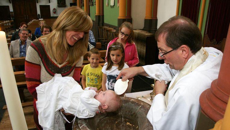 Van den Hout tijdens een doop in de H. Hubertuskerk in Alem. Beeld