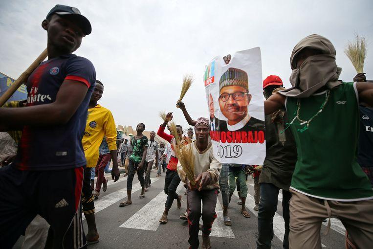 Aanhangers van de Nigeriaanse president Muhammadu Buhari vieren in Kano zijn herverkiezing. Beeld  REUTERS/Afolabi Sotunde