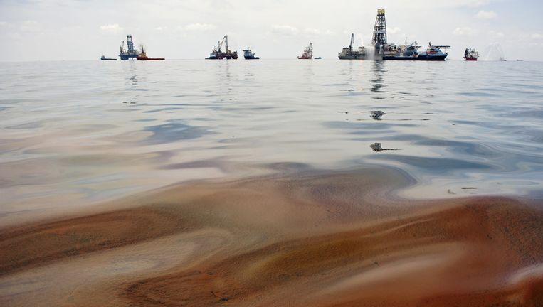 Olie op het water in de Golf van Mexico, met op de achtergrond de plek waar het olieplatform is gezonken, voor de kust van Louisiana. FOTO ANP Beeld