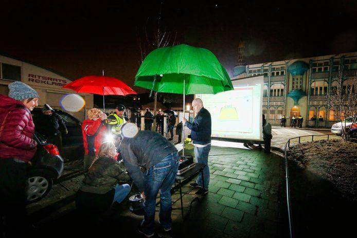 Pegida-aanhangers bouwen een projectiescherm op met de Abi Bakr Issidik moskee op e achtergrond.