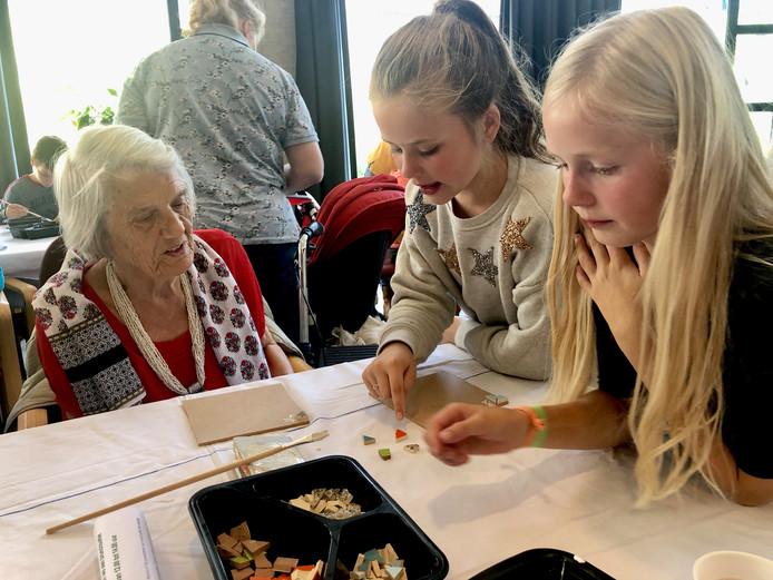 Leerlingen van basisschool Helder Camara in Teteringen knutselen samen met ouderen van Park Zuiderhout aan mozaïektegels, in het kader van het 50-jarig bestaan van de school.