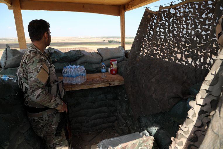 Een SDF-strijder houdt toezocht op de Turkse grens. Beeld EPA