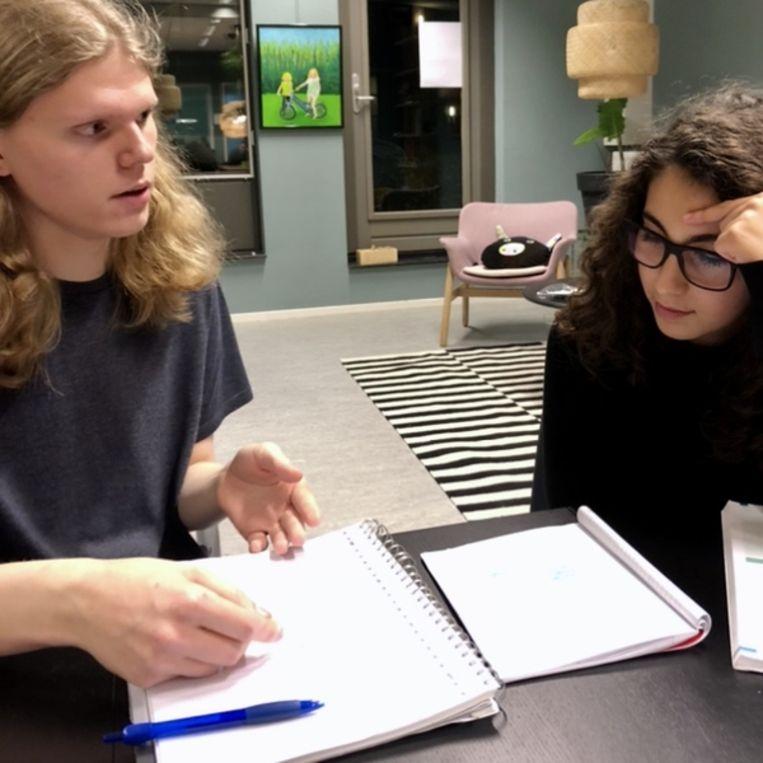 Student Gijs helpt Chaima met natuurkunde Beeld null