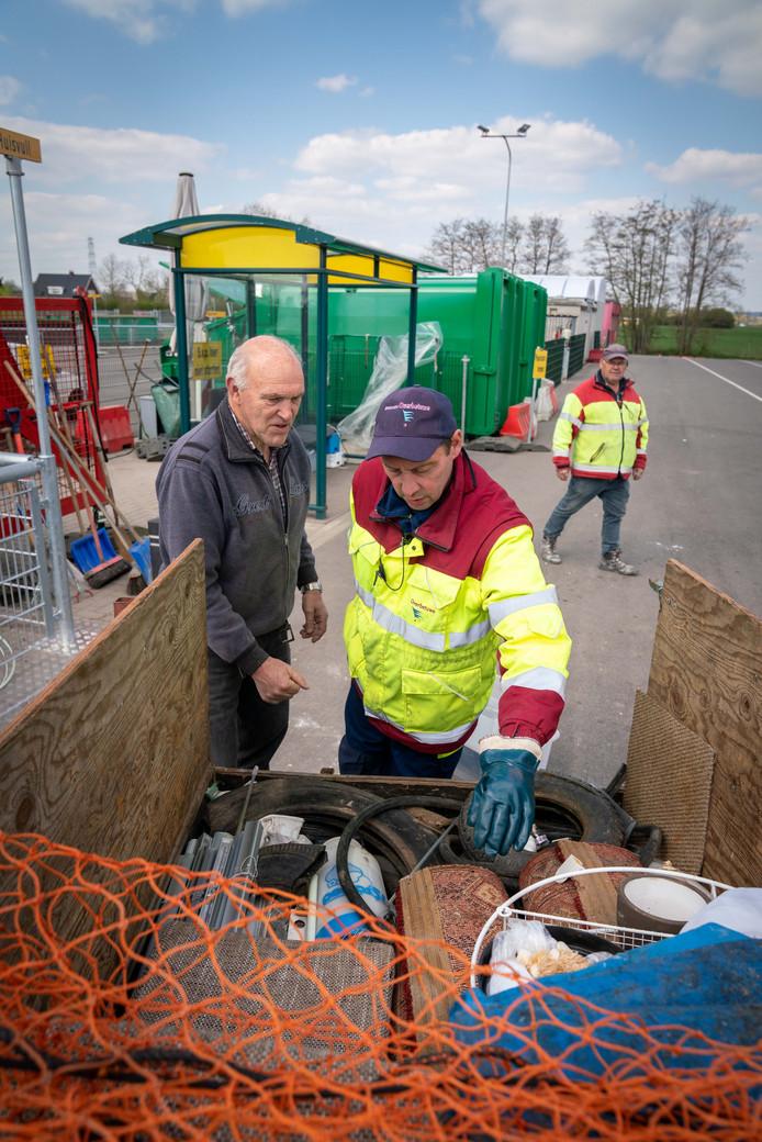 Een medewerker van de milieustraat controleert het aangeboden afval voor het in de containers verdwijnt.