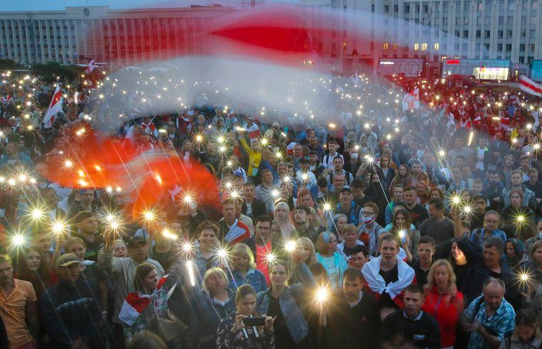 Lichtjes en vlaggezwaai voor het regeringsgebouw in Minsk, waar de oppositie demonstreert tegen de Wit-Russische president Loekasjenko. Beeld AP