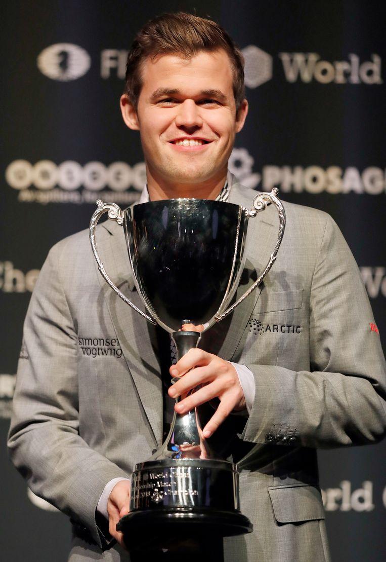 Carlsen poseert met zijn trofee.  Beeld AP