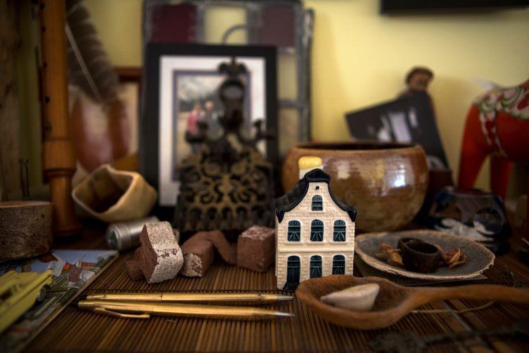Detail van het altaartje in Tagan Enroue's huis. De twee pennen zijn van haar opa geweest, die hij altijd in zijn borstzakje droeg. De stukjes steen zijn overblijfselen van Hotel Wijnberg toen het werd afgebroken. Tegen de muur staat een klein glas-in-loodraampje, ook afkomstig uit het hotel.   Beeld Chantal Heijnen
