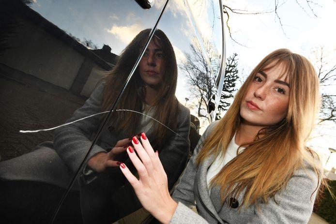 Kim van der Wielen bij haar beschadigde auto.
