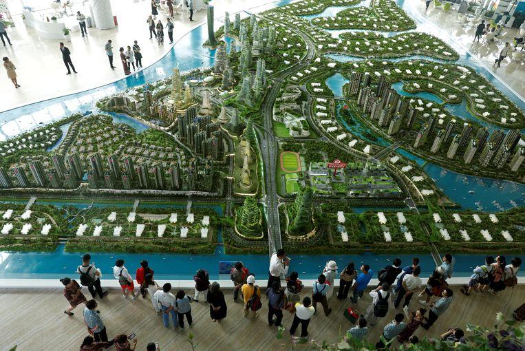 Belangstellenden bekijken een maquette van het project Forest City in de Maleisische stad Johor Bahru. Beeld Edgar Su / Reuters