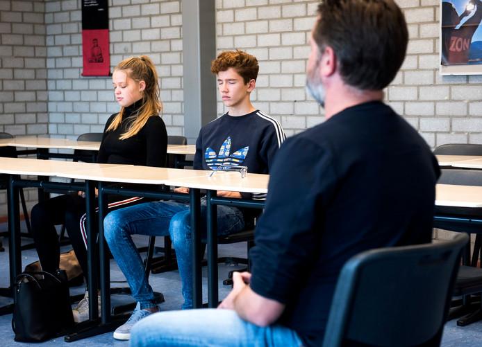 Na de lessen mediteren de leerlingen onder leiding van docent Jochem Quartel (r). Ze doen dit om even te ontsnappen aan de dagelijkse deadlines en stress.
