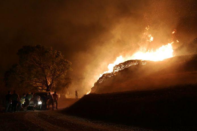 Bosbranden Portugal. Een auto, die vast kwam te zitten en wordt gebruikt om water te brengen naar vrijwilligers, wordt weggeduwd.
