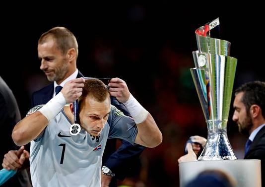 Terwijl hij zijn medaille meteen van zijn nek haalt, loopt Jasper Cillessen gedesillusioneerd langs de trofee.