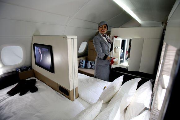 Een stewardess laat een nagebouwde suite zien