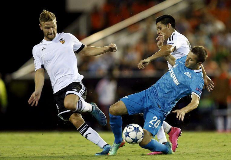Perez (rechts) en Mustafi (links) van Valencia met middenvelder Fayzulin van Zenit. Beeld epa