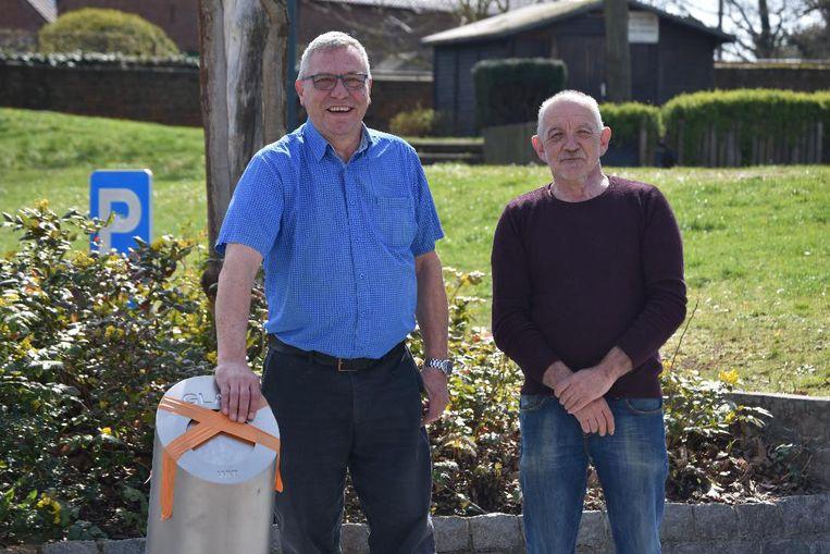 Schepenen Stef Ryckmans (links) en René De Becker bij de - nu nog afgeplakte - ondergrondse glascontainers in Everberg.