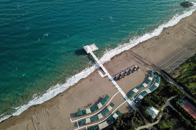 Eind juni, een strand in Antalya. Normaal gesproken moet je er 's ochtends heel vroeg bij zijn om een plekje te bemachtigen. Nu ligt het toerisme zo goed als stil. Beeld AFP