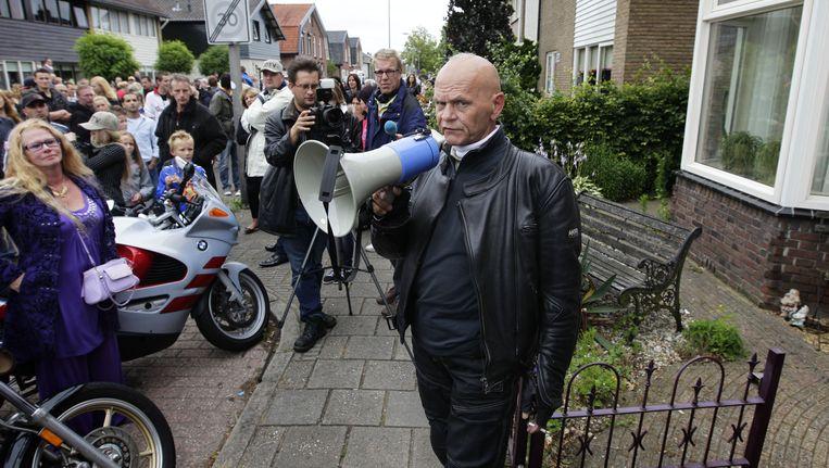 Jos Aalders (met megafoon) van Partij Rechten Kind heeft het woord voor het huis van een bestuurslid van pedovereniging Martijn tijdens de protestmars van Partij Rechten Kind zondag in Hengelo. Beeld anp