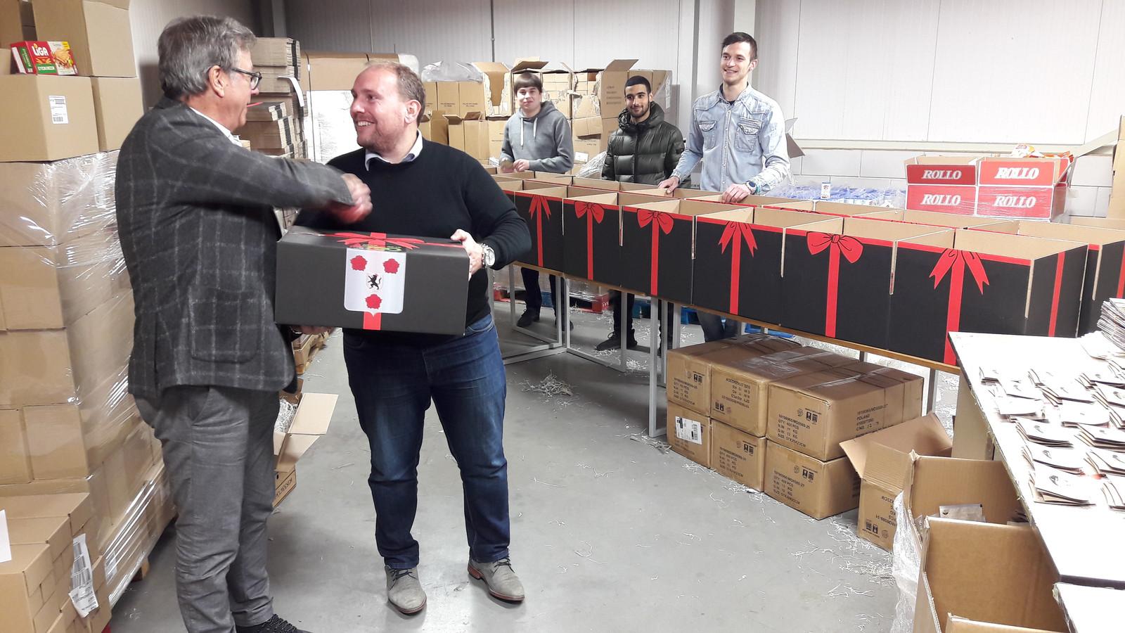 Cor Verbogt (links) krijgt het eerste kerstpakket van Robert Breedveld van Looma in Roosendaal. Medewerkers van Looma kijken toe.