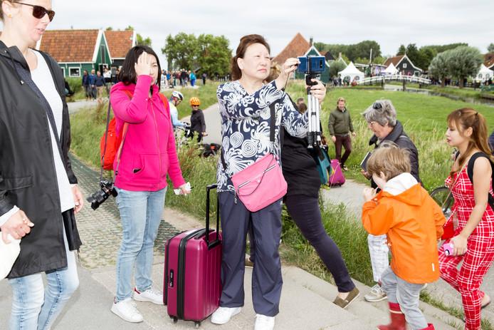 Chinese toeristen op de Zaanse Schans. Amsterdam spreidt het toerisme graag uit over de regio.