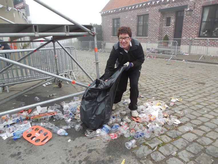 Marleen Beck ruimt het afval voor haar deur op.